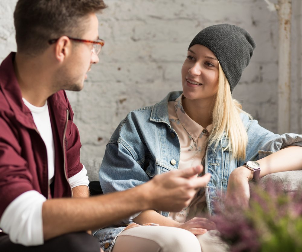 Young hipster couple talking in cozy cafe