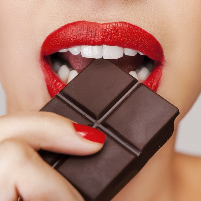 Indulging in a sweet affair with chocolate. Close-up of a beautiful women holding finger on her red lips while standing against grey background