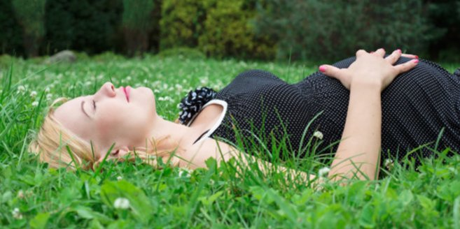 Cerclage: schwangere Frau liegt im Gras