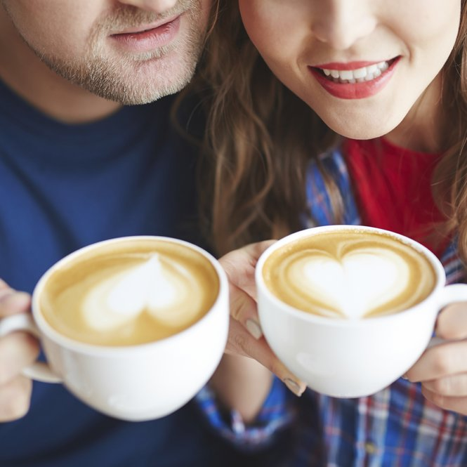 Amorous dates holding cups with coffee