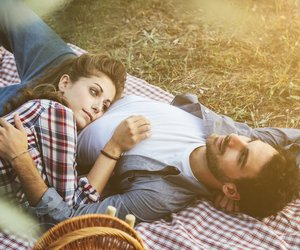 On a beautiful late summer day, a couple of young and beautiful lovers is lying on a towel on the grass. The head of the young woman is on the belly of her boyfriend. Picture taken from the leaves of olive trees in a field the Tuscany, Italy