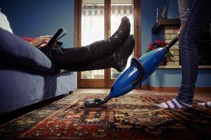Frauen putzt, Mann sitzt auf Sofa
