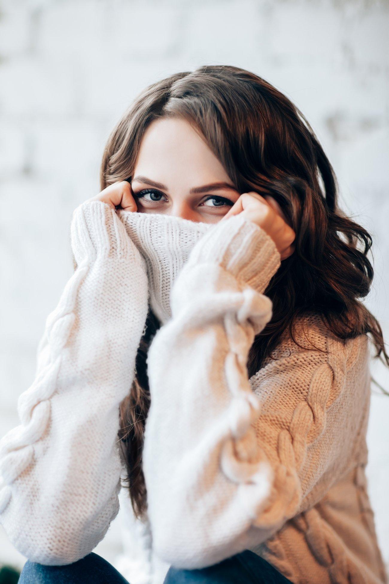 Frau kuschelt sich in ihren Pullover
