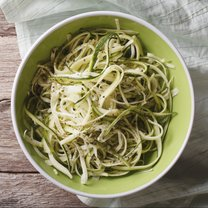 Useful raw zucchini pasta in a bowl close up on the table. horizontal top view