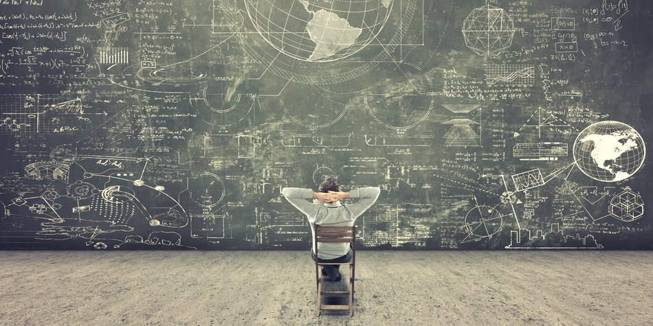 Businessman sitting on a chair and studying math formulas on blackboard