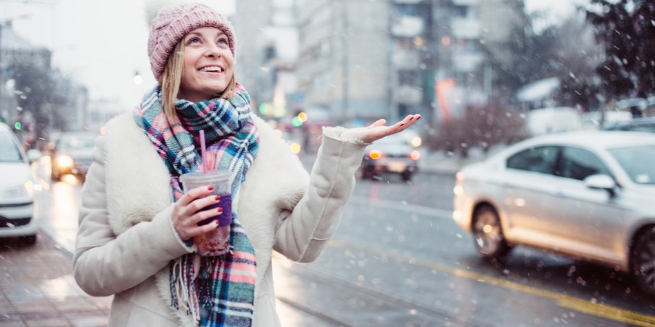 Young women on city street enjoy in snow falling and drinking healthy smoothie