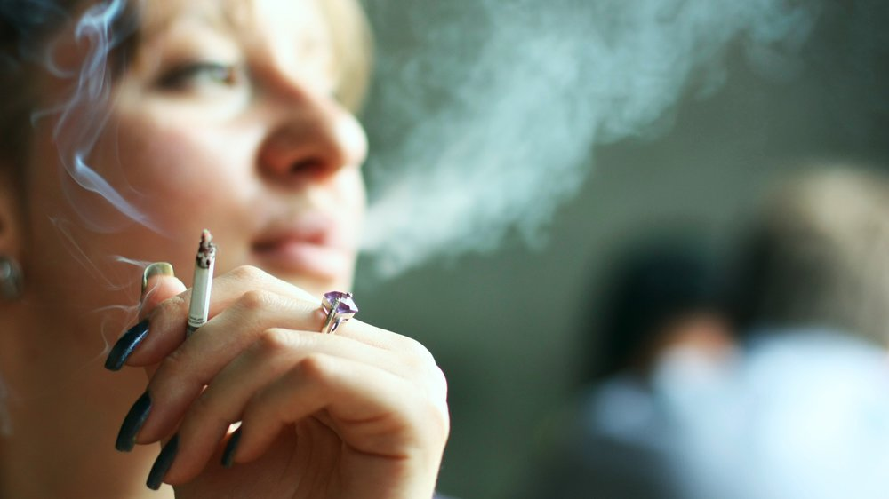 young woman smoking cigarette. Focus on hand
