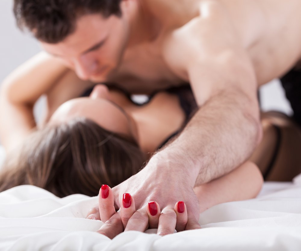 Portrait of young couple making love in bed