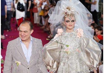 Designer Christian Lacroix mit einem Model auf einer Fashion Show