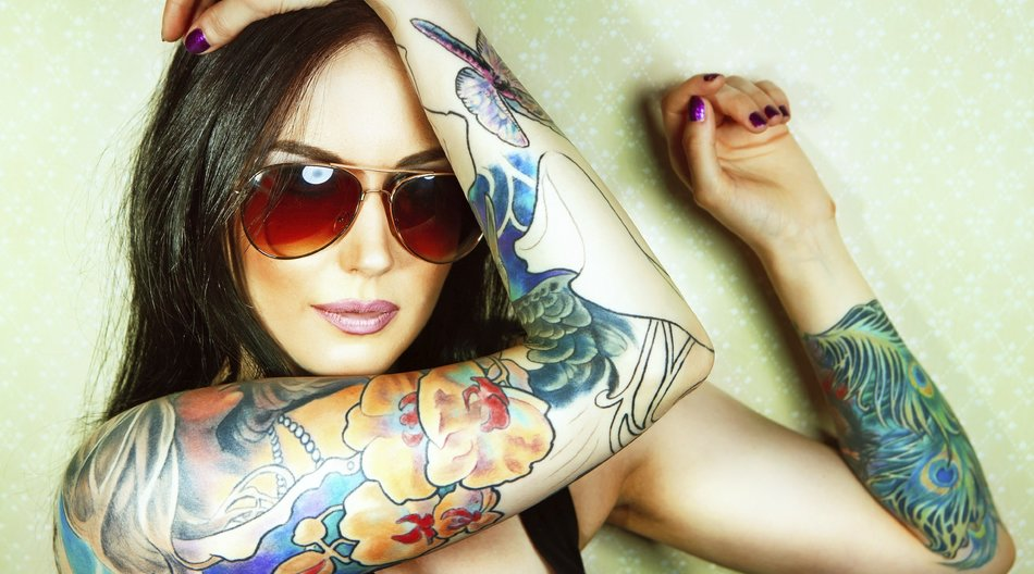 Beautiful girl with stylish make-up and tattooed arms. tattoo