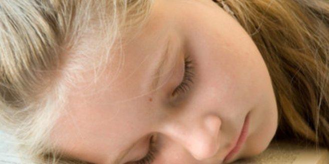 Lernen im Schlaf: Mädchen schläft auf Buch