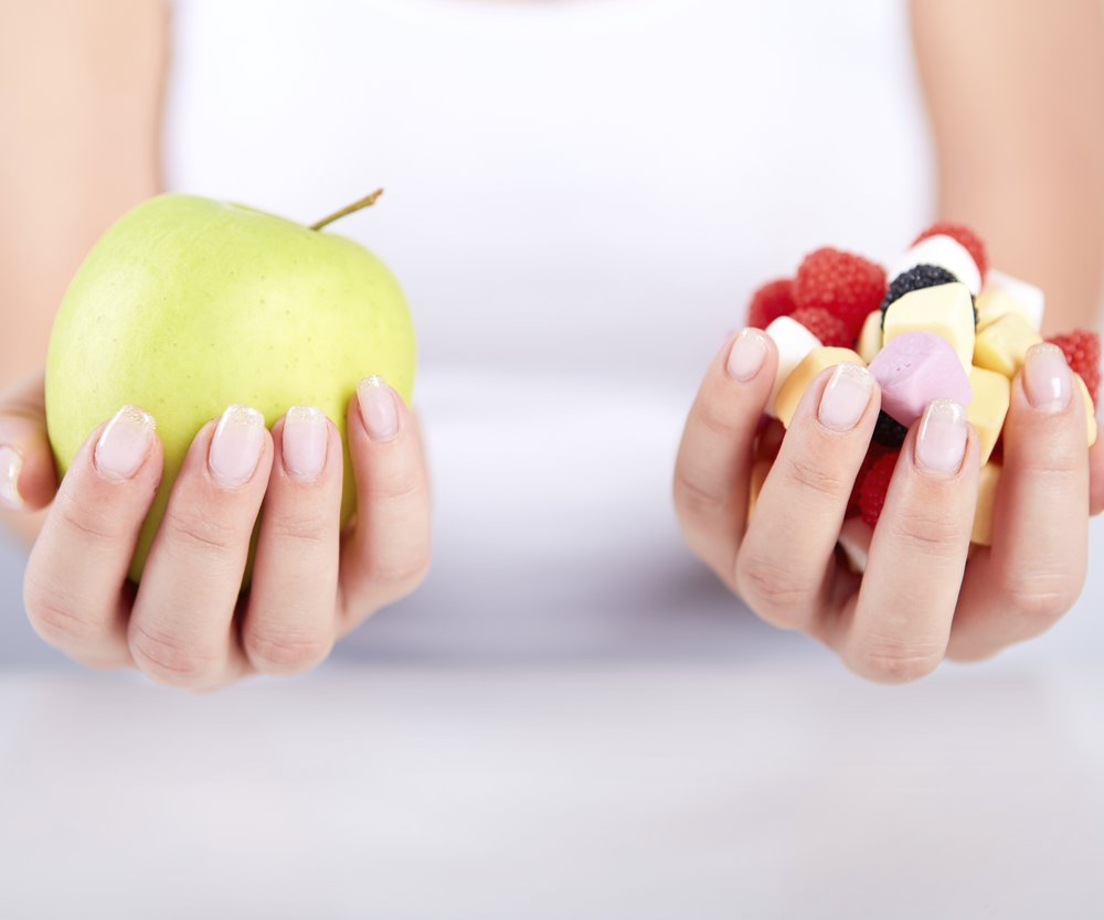Woman holding apple in her hand and in the other hand candies