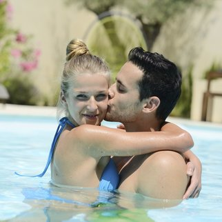 lovely beautiful young couple playing together in a holiday resort swimming pool
