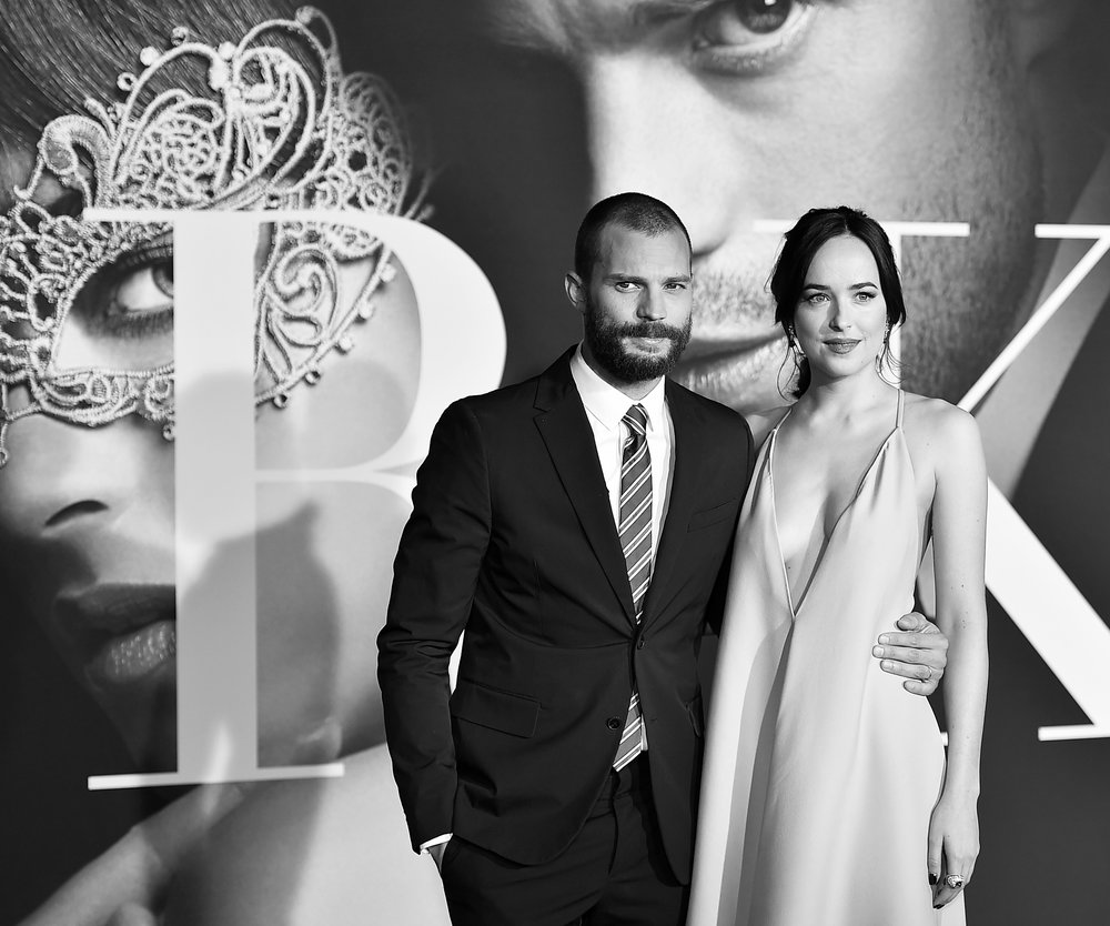 "LOS ANGELES, CA - FEBRUARY 02: (EDITORS NOTE: Image has been converted to black and white.) Actors Jamie Dornan and Dakota Johnson attend the premiere of Universal Pictures' ""Fifty Shades Darker"" at The Theatre at Ace Hotel on February 2, 2017 in Los Angeles, California. (Photo by Alberto E. Rodriguez/Getty Images)"