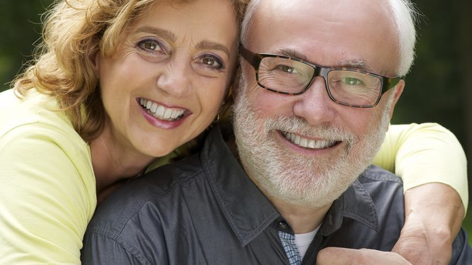 Close up portrait of a happy husband and wife smiling outdoors