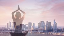 Double exposure of woman practicing yoga and city background with office building, concept about revitalizing in modern business life