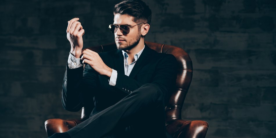 Young handsome man in suit and sunglasses adjusting sleeve on his shirt while sitting in leather chair against dark grey background