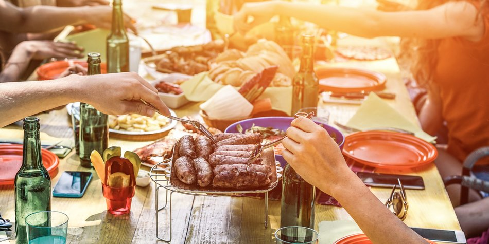 Group of happy friends eating and drinking beers at barbecue dinner at sunset - Adult people having meal together outdoor - Focus on fork sausages - Summer lifestyle, food and friendship concept
