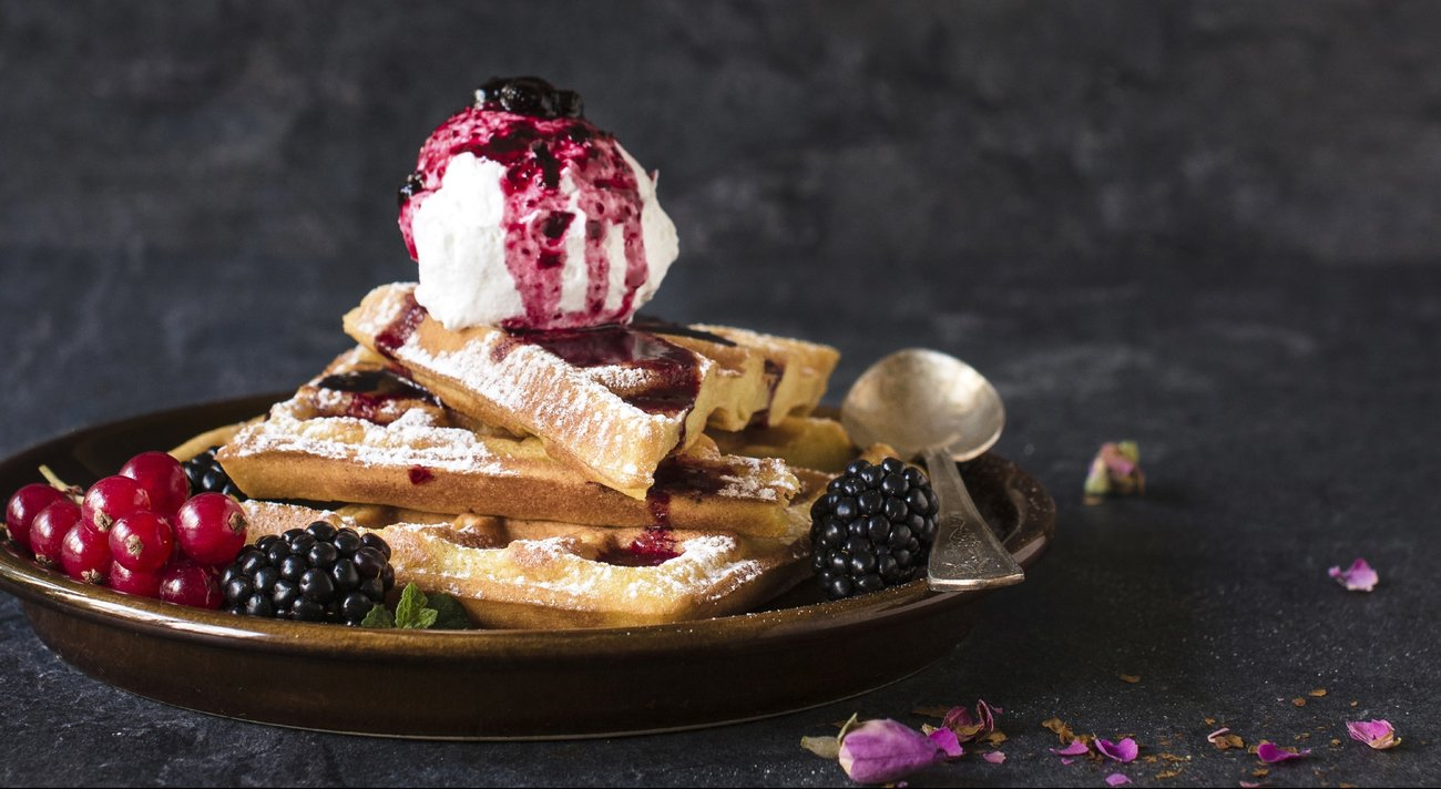 Baked traditional Belgium waffles with ice cream and berry fruit sauce,selective focus and blank space