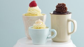 Vanilla and chocolate mug cakes with frosting and raspberries on a cake stand