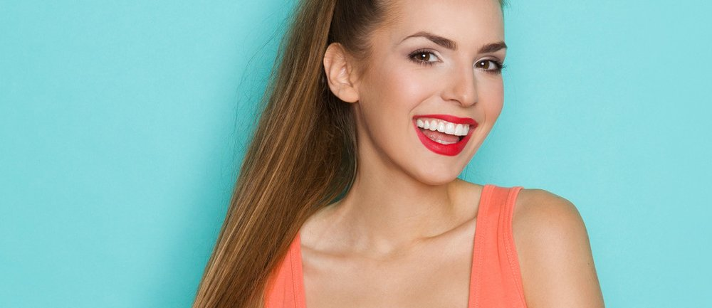 Sexy young woman in orange shirt with cleavage pulling ponytail and smiling. Three quarter length studio shot on teal background.