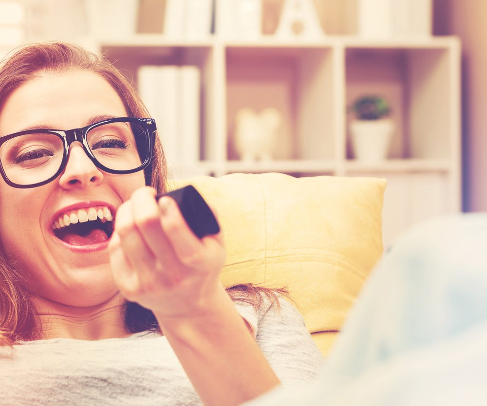 Young woman laughing while watching TV in the living room