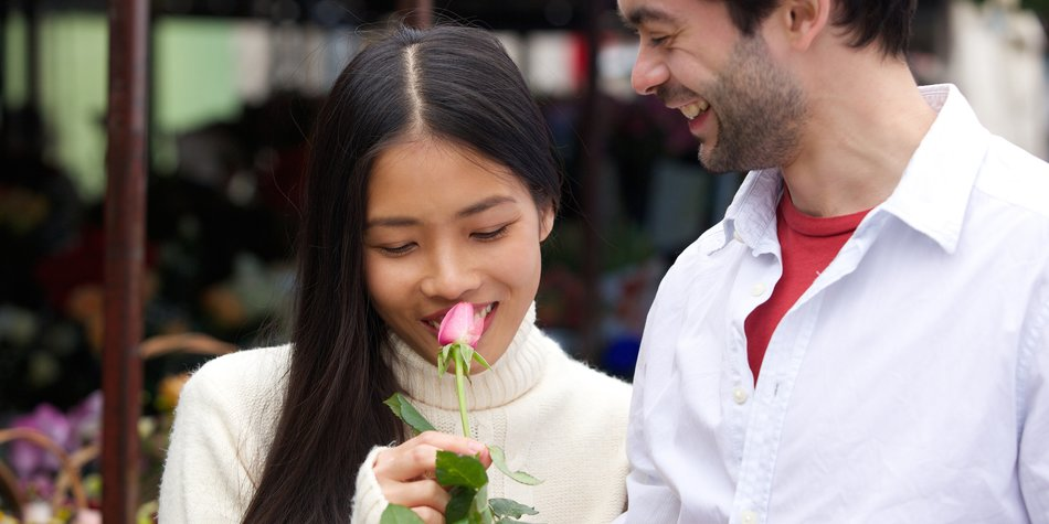 Close up portrait of a beautiful young woman smelling rose with boyfriend smiling