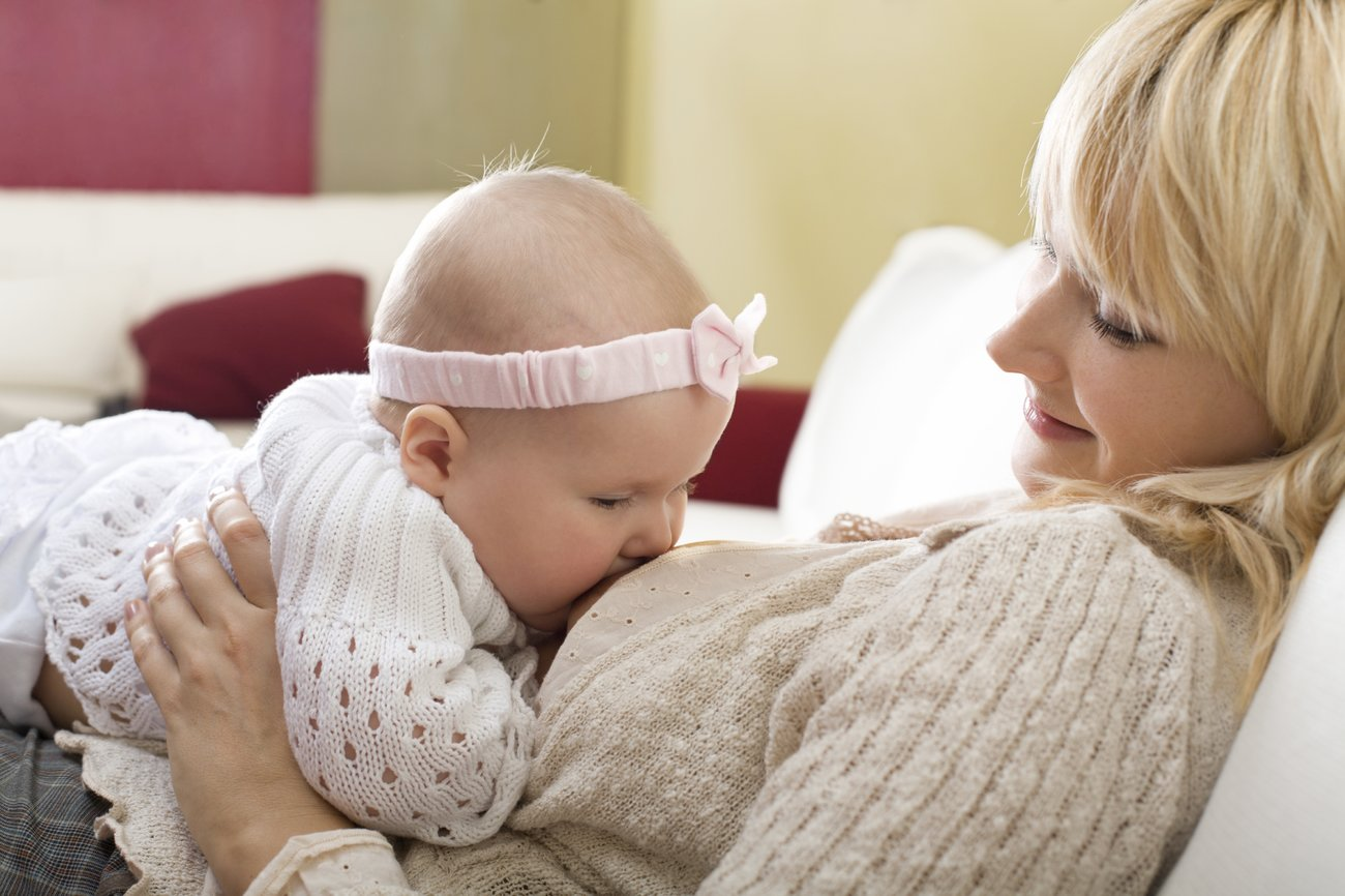 Mother breast feeding her baby girl at home