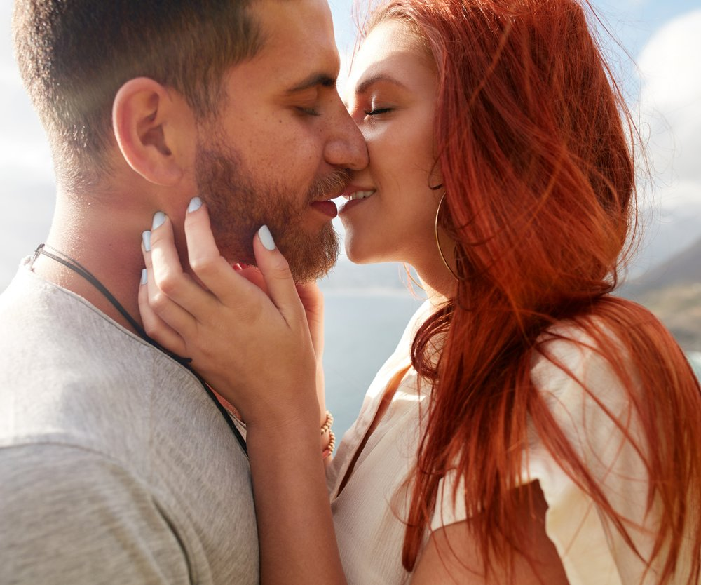 Close up shot of affectionate young couple embracing and kissing outdoors.