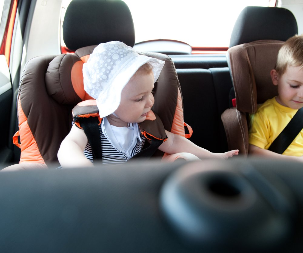 Little brother and his baby sister travelling in baby car seats