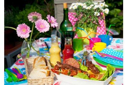 Die perfekte Vorbereitung für eine Grillparty beinhaltet Brot, Grillfleisch, Salate, Saucen und Marinaden