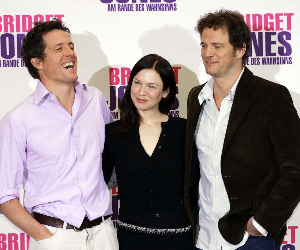 """BERLIN - NOVEMBER 11: Hugh Grant (l.), Renee Zellweger (c.) and Colin Firth (r.) pose at the photocall to promote """"Bridget Jones: The Edge of Reason"""" at Hotel Adlon on November 11, 2004 in Berlin, Germany. (Photo by Carsten Koall/Getty Images)  *** Local Caption *** Renee Zellweger;Hugh Grant, Colin Firth"""