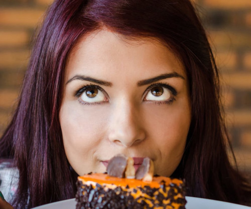 young girl or woman contemplating whether to eat cake or not. Teenager crouched beside the table and looks at cake