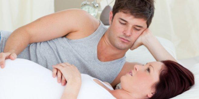 Schwanger nach Fehlgeburt: Schwangere Frau und Partner liegen im Bett
