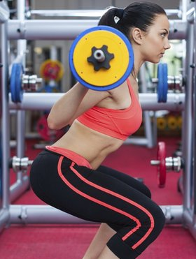 Woman in gym sport exercising squating with barbell lifting weights, young girl working out