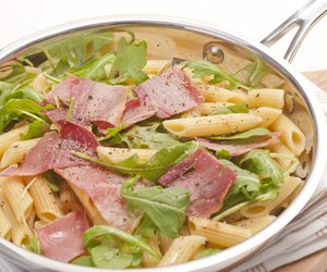 Pasta (penne) with aragula (rocket) and crispy prosciutto in a pan.