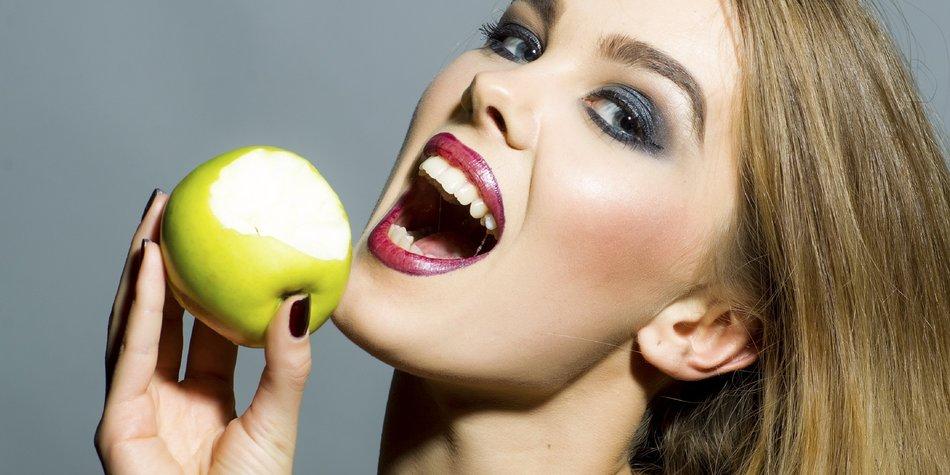 Eine Frau möchte in einen Apfel beißen