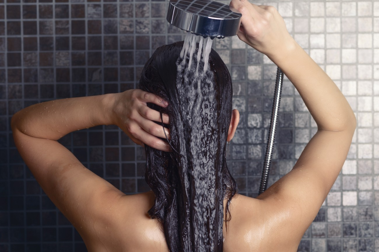 Young woman washing her long hair under the shower standing with her back to the camera rinsing it off under the jet of water with her head partially turned to the side, over grey mosaic tiles