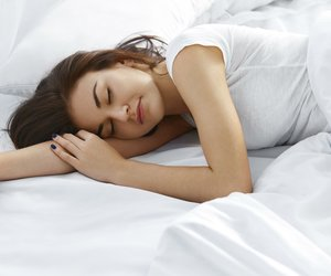 Attractive young woman sleeping in bedroom. Healthy lifestyle. Wellness concept