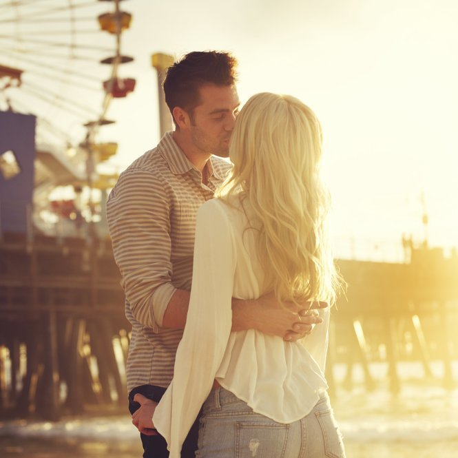 young romantic couple kissing in front of sunset in santa monica