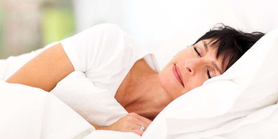 cute mature woman sleeping on bed
