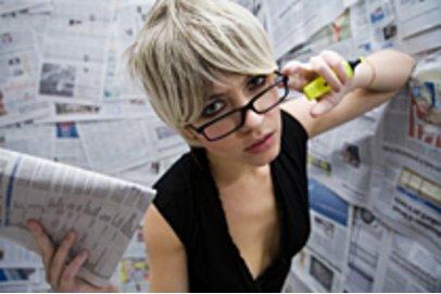 Frau unter Zeitungen