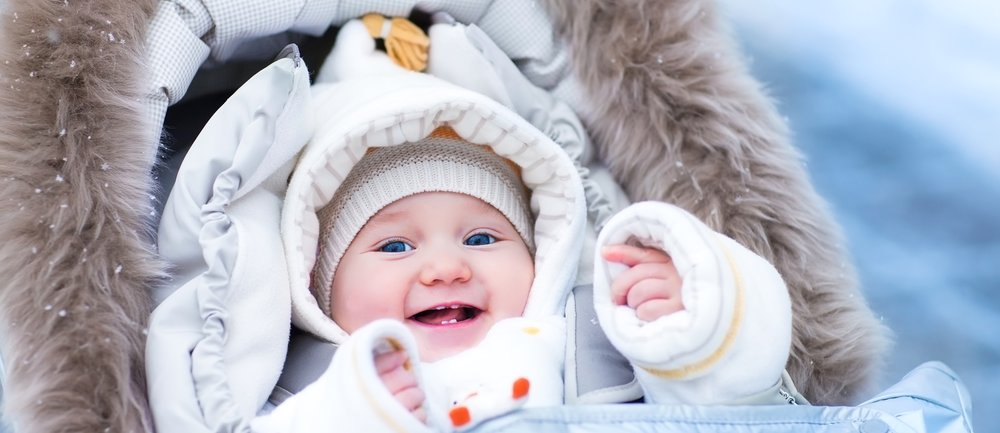 Happy laughing baby girl enjoying a walk in a snowy winter park sitting in a warm stroller with sheepskin hood wearing a white jacket and hat