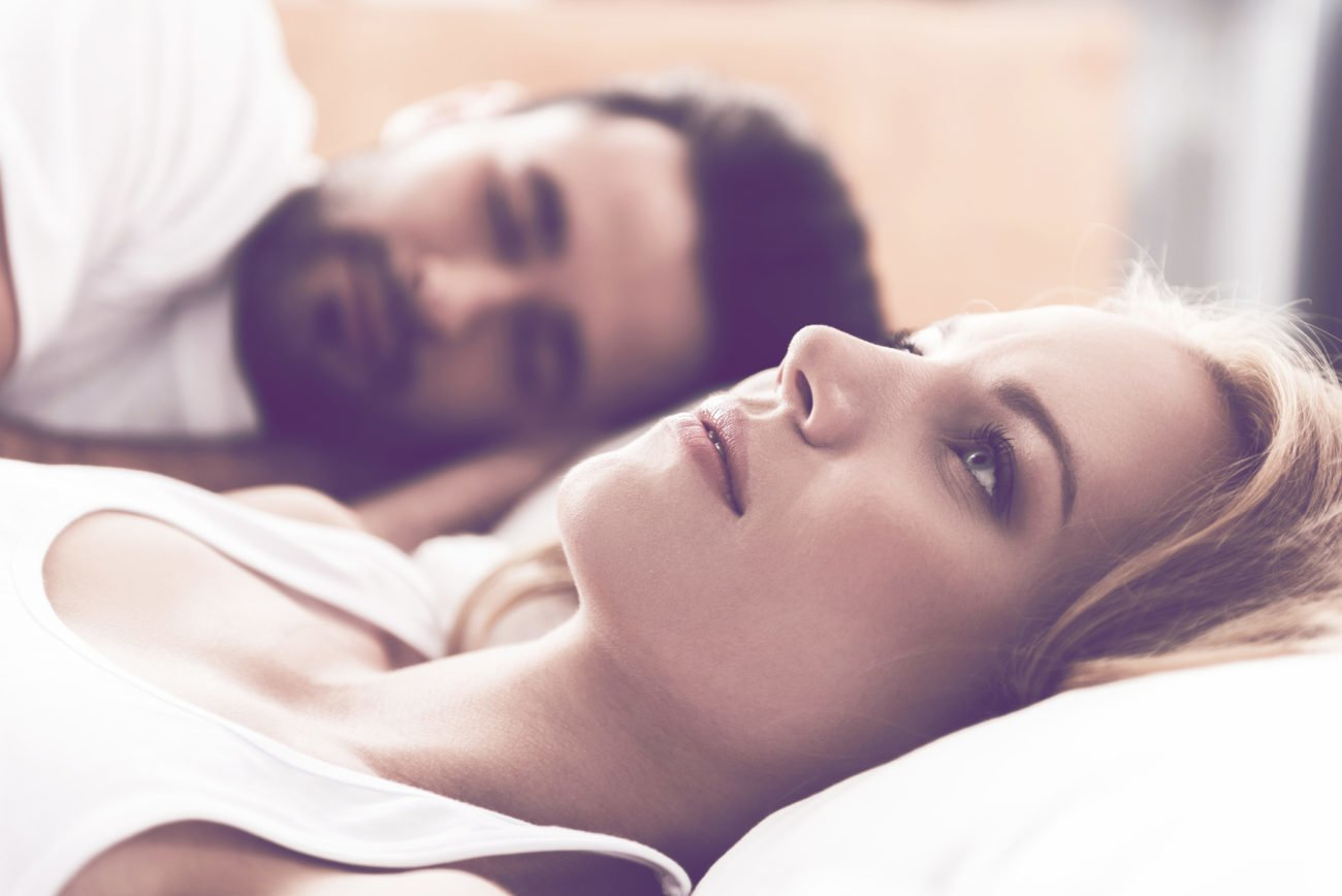 Frau liegt nachdenklich im Bett