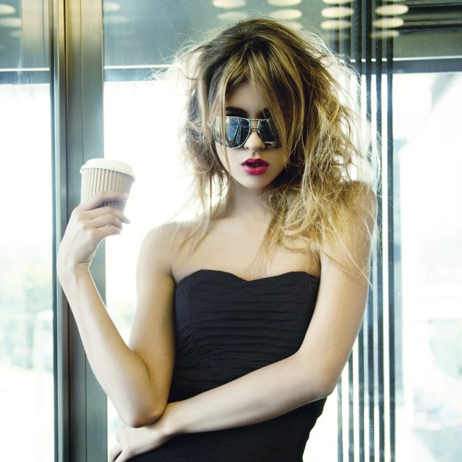 picture of girl posing in elevator with cup of coffee