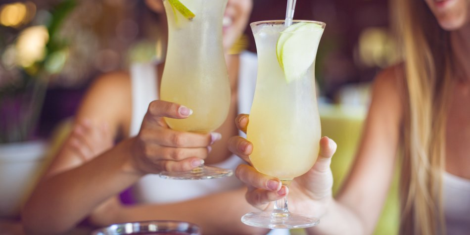Two beautiful women having fun in a bar drinking cocktails