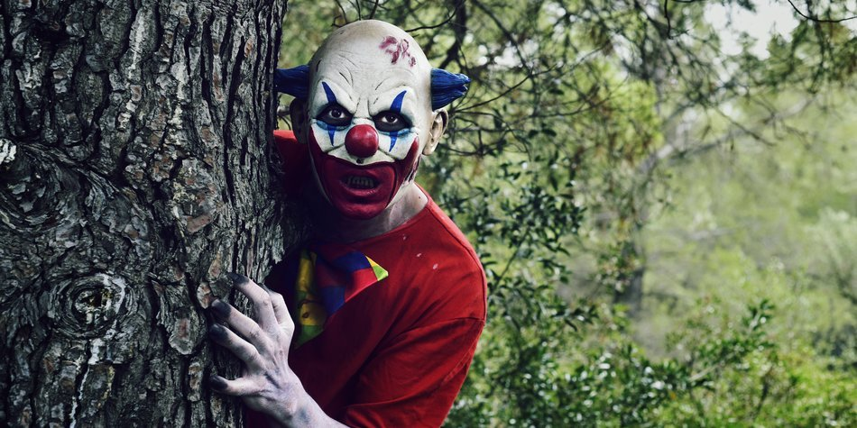 closeup of a scary evil clown in the woods, emerging from behind of a big tree