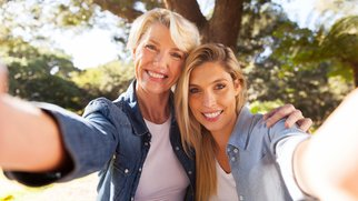 happy senior woman and daughter taking selfie together