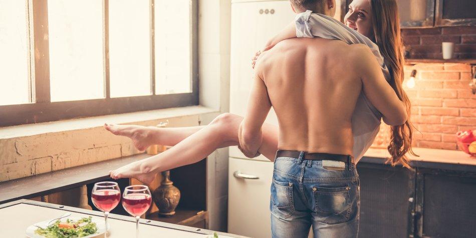 Mann trägt Frau in der Küche