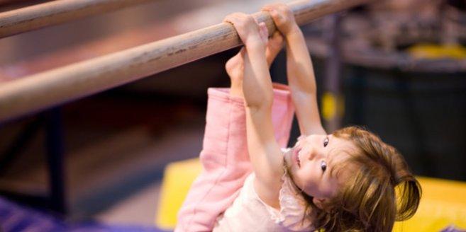 Eltern-Kind-turnen: Kleines Mädchen turnt am Barren